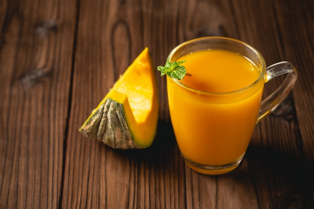 Fresh pumpkin juice in glass on wooden table. Free Photo