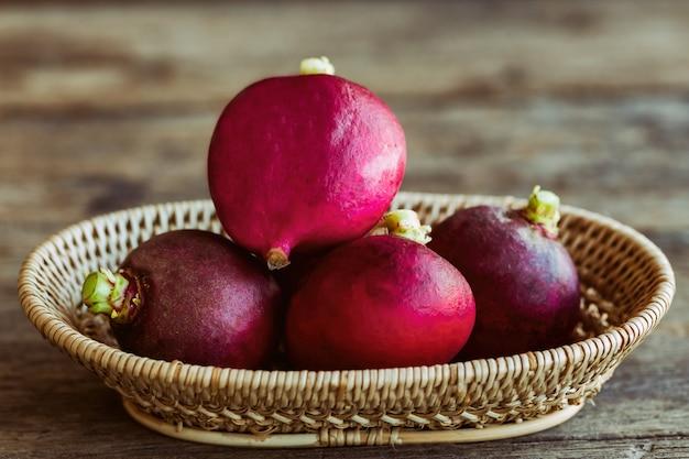 Fresh radish in wood basket put on wooden table Premium Photo