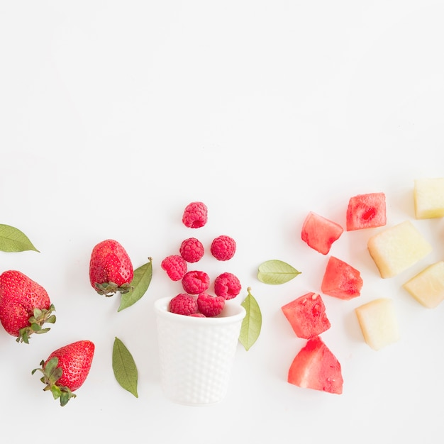 Fresh raspberries spilled front glass with strawberry; watermelon and pineapple isolated on white background Free Photo