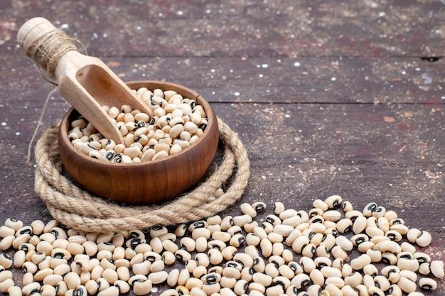 茶色のボウルの中の新鮮な生豆と茶色全体に広がる、食品生豆ハリコット写真 無料写真