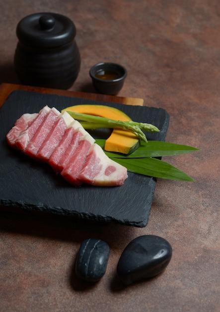 Fresh raw beef brisket slice with pumpkin pieces and asparagus on the black dish rock ,menu set. Premium Photo