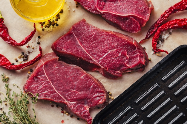 Fresh raw beef meat steak slices with spices and olive oil ready for cooking Premium Photo