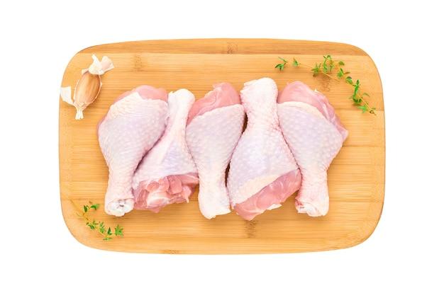 Свежие сырые куриные голени на деревянной доске Premium Фотографии