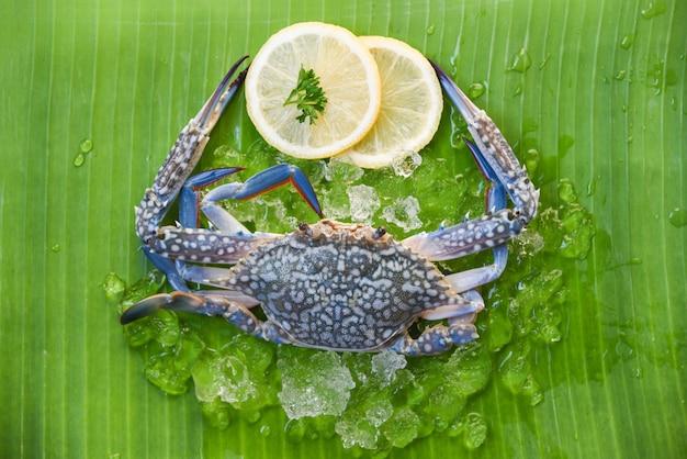 Fresh raw crab seafood with ice and lemon on banana leaf Premium Photo