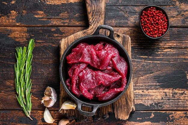 Свежие сырые нарезанные кубиками ломтики филе красной говядины в чугунной сковороде Premium Фотографии