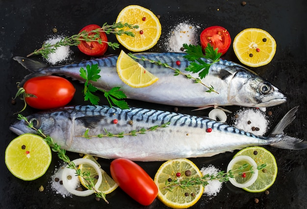 Fresh raw mackerel with vegetables on a black metal background Premium Photo