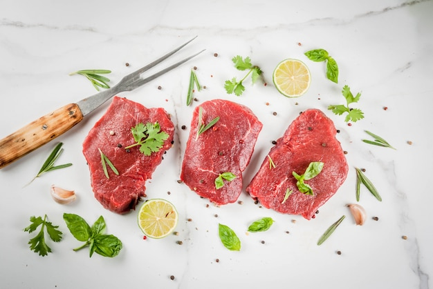 Fresh raw meat. beef tenderloin, steaks, on a white marble table. with olive oil, spices for cooking - basil, rosemary, coriander, parsley, garlic, lemon, salt, pepper. copy space top view Premium Photo
