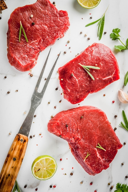 Fresh raw meat. beef tenderloin, steaks, on a white marble table. with olive oil, spices for cooking  basil, rosemary, coriander, parsley, garlic, lemon, salt, pepper. top view copyspace Premium Photo