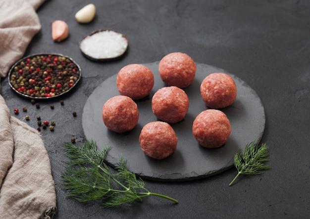 ローズマリーとパセリと黒の表面に唐辛子、塩、ニンニクをラウンドボードに新鮮な生ミンチ牛肉のミートボール。 Premium写真