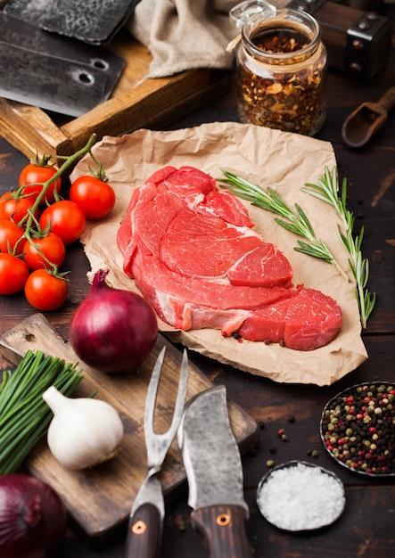 Свежий сырой органический ломтик тушеного филе на мясной бумаге с вилкой и ножом на темном деревянном Premium Фотографии