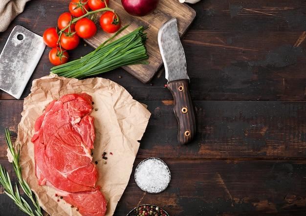Свежий сырой органический ломтик тушеного филе на мясной бумаге с вилкой и ножом Premium Фотографии