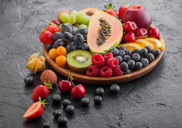 Fresh raw organic summer berries and exotic fruits in round wooden plate. papaya, grapes, nectarine, orange, raspberry, kiwi, strawberry, lychees, cherry. top view Premium Photo