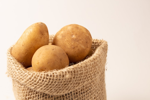 Fresh and raw potatoes in a rustic sack isolated on white backgroud.. Premium Photo