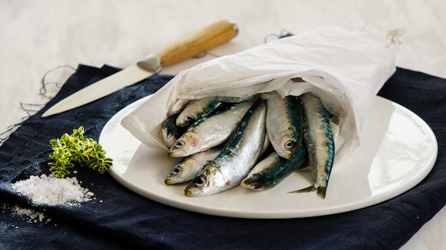 Fresh raw sardines with salt and herbson the white plate Premium Photo