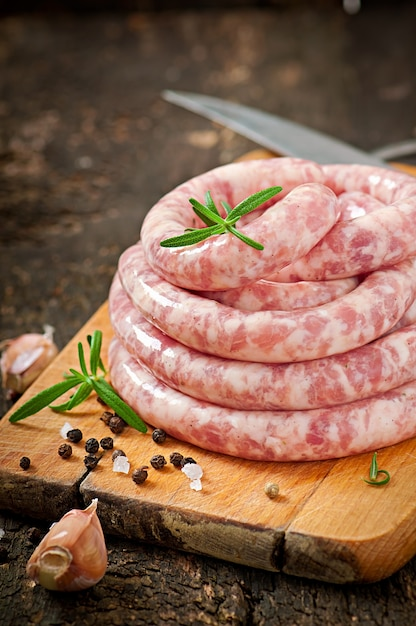 Fresh raw sausage on the old wooden Free Photo