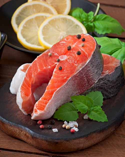 Fresh and raw steaks trout on a wooden cutting board with sliced lemon, rosemary and pepper Free Photo