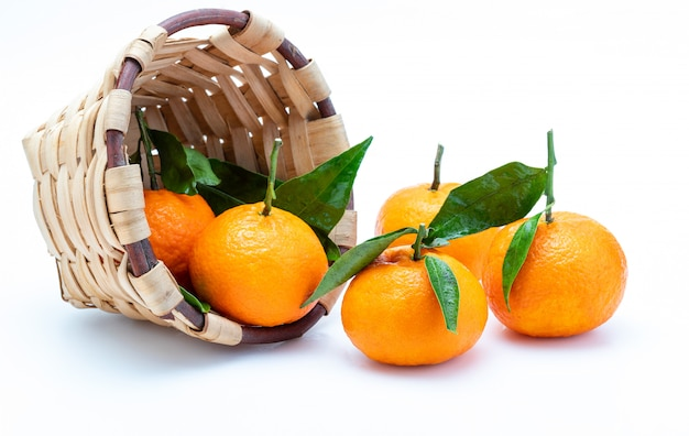 Fresh and raw tangerines with green leaves in rustic wicker basket. isolated Premium Photo