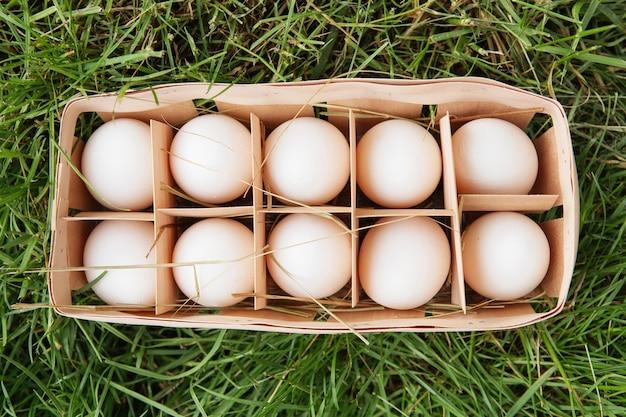 Fresh raw white chicken eggs in a wooden box on green grass Premium Photo