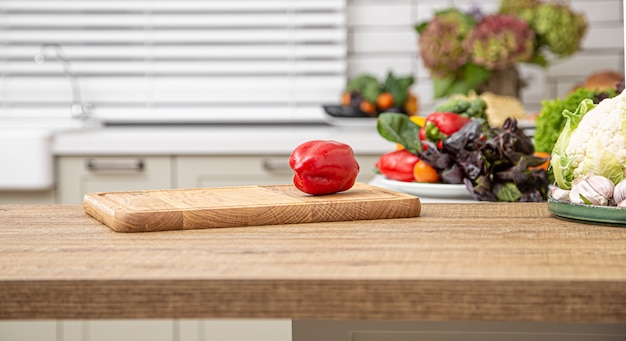 Fresh red bell pepper on a wooden plank against the background of a kitchen interior. Free Photo