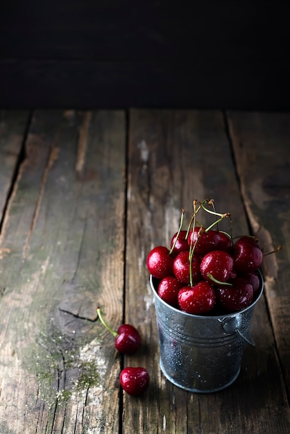 Fresh red cherries on wooden table with water drops Premium Photo