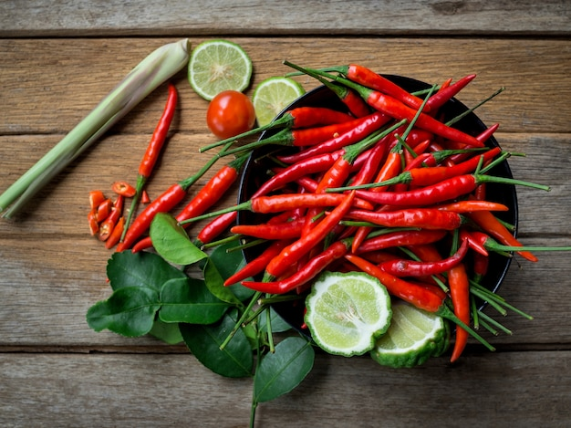 Fresh red chili peppers in a black cup on old wood table background. top view Premium Photo