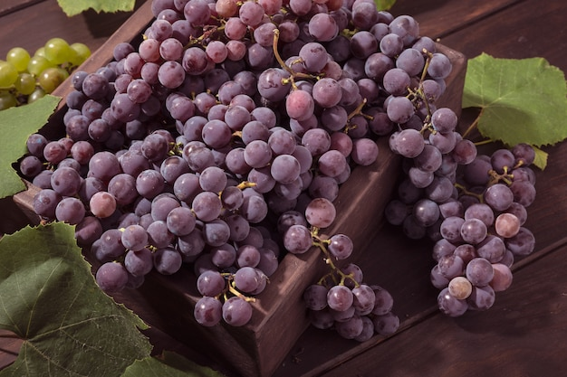 Fresh red grapes in crate on wooden table Premium Photo