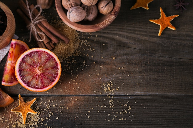 Fresh red orange fruit, anise, cinnamon and walnuts Premium Photo
