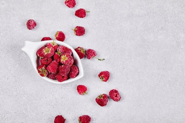 白い表面の白いボウルに新鮮な赤いラズベリー。上面図。 無料写真