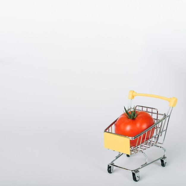 Fresh red tomato in shopping cart on white surface Free Photo