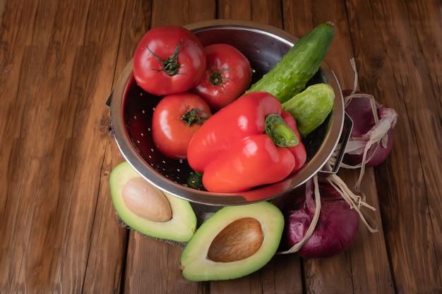 Свежие красные помидоры, сладкий перец, огурцы, красный лук и авокадо на деревянном фоне Premium Фотографии