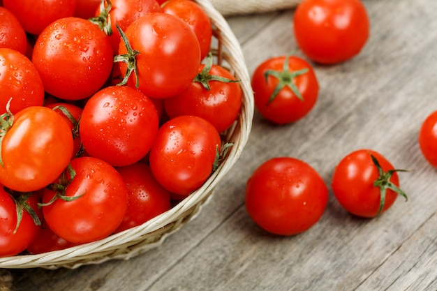 Fresh red tomatoes in a wicker basket on an old wooden table. ripe and juicy cherry tomatoes with drops of moisture, gray wooden table, around a cloth of burlap. in a rustic style. Premium Photo