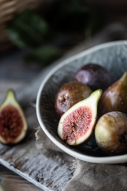 Fresh ripe figs in a bowl on a dark wooden table. Premium Photo