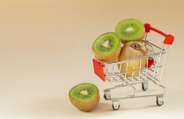 スーパーマーケットのカートで新鮮な熟したキウイ。テキスト用のスペース Premium写真