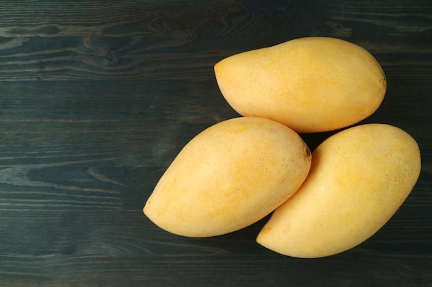 Fresh ripe thai nam dok mai mangoes on dark wood Premium Photo