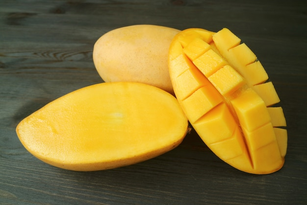 Fresh ripe thai nam dok mai mangoes whole fruit and cut in half on dark brown wood Premium Photo
