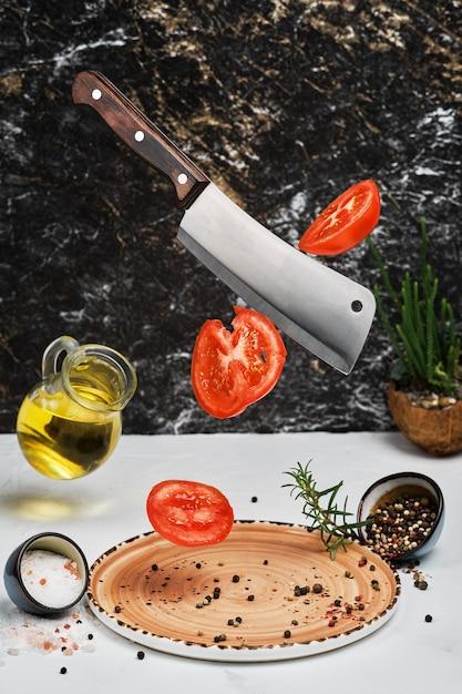 I pomodori freschi maturi vengono tagliati con un coltello e lasciati cadere sul piatto con rosmarino, sale, pepe e olio d'oliva Foto Gratuite