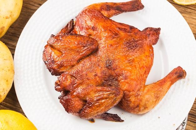 Pollo arrosto fresco su una tavola di legno Foto Gratuite