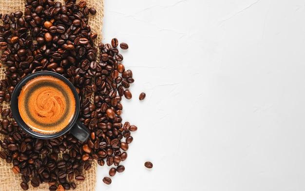 갓 볶은 커피 원두와 거품이있는 뜨거운 에스프레소 한잔, 넓은 콘크리트 흰색 표면의 왼쪽에 위치 무료 사진
