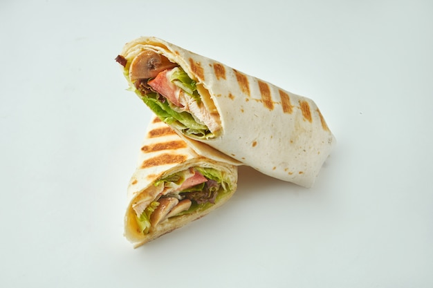 Fresh roll with chicken, tomatoes, cheese and lettuce in pita bread on a white table. baked chicken shawarma Premium Photo