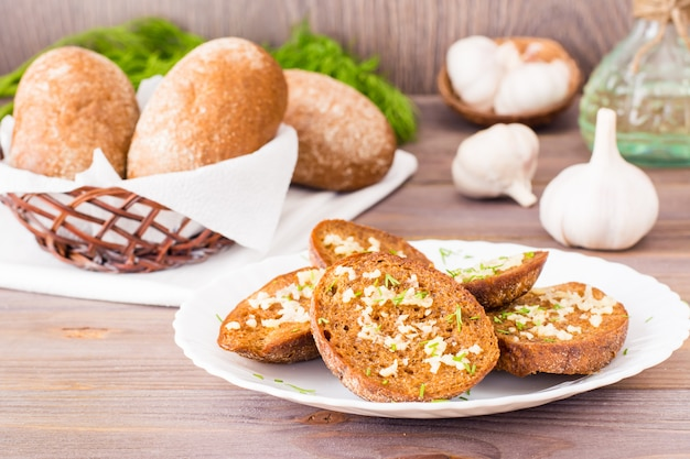 Fresh rye garlic croutons with dill on a plate on a wooden table Premium Photo