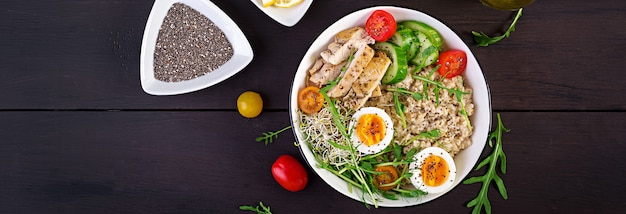Fresh salad. breakfast bowl with oatmeal, chicken fillet, tomato, lettuce, microgreens and boiled egg. healthy food. vegetarian buddha bowl. Free Photo