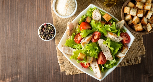 Fresh salad made of tomato, ruccola, chicken breast, eggs, arugula, crackers and spices. caesar salad in a white, transparent bowl on wooden background Premium Photo