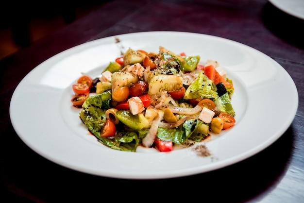 白い皿に新鮮なサラダ。飲食店。 Premium写真