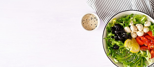 Fresh salad with avocado, tomato, olives and mozzarella in a bowl Free Photo