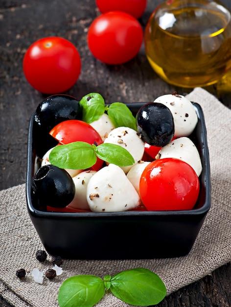 Fresh salad with cherry tomatoes, basil, mozzarella and black olives. Free Photo