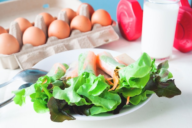 Fresh salad with egg and milk, healthy menu with red dumbbell, healthy lifestyle concept Free Photo