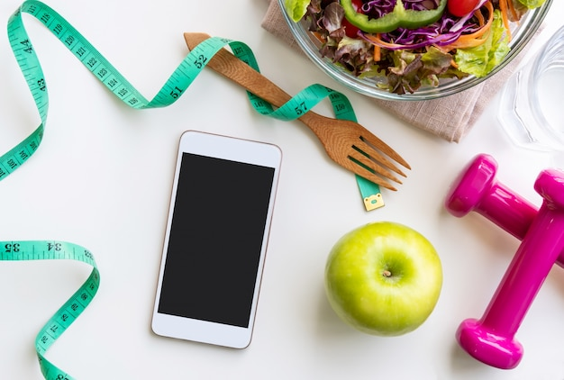 Fresh salad with green apple, dumbbell, measuring tape and empty screen smartphone Premium Photo