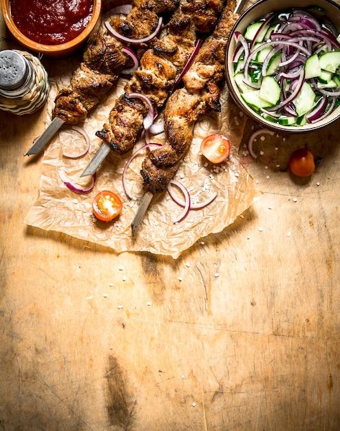 シシカバブの串焼きフレッシュサラダ。木製のテーブルの上。 Premium写真