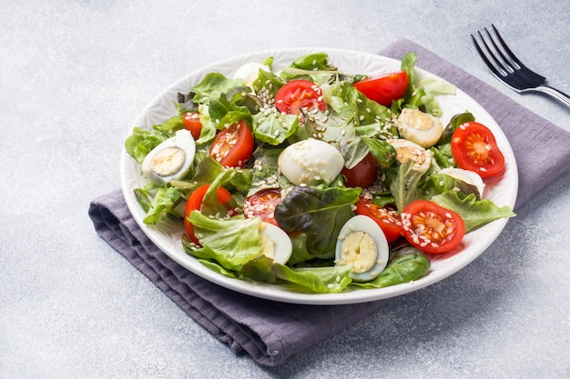 Fresh salad with tomatoes and quail eggs and lettuce. Premium Photo