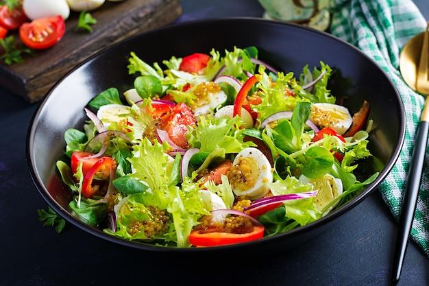 Свежий салат с овощами, помидорами, красным луком, листьями салата и перепелиными яйцами. концепция здорового питания и диеты. вегетарианская пища. Бесплатные Фотографии